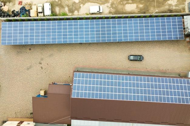 Widok z lotu ptaka na elektrownię słoneczną z niebieskimi panelami fotowoltaicznymi zamontowanymi na dachu budynku przemysłowego.