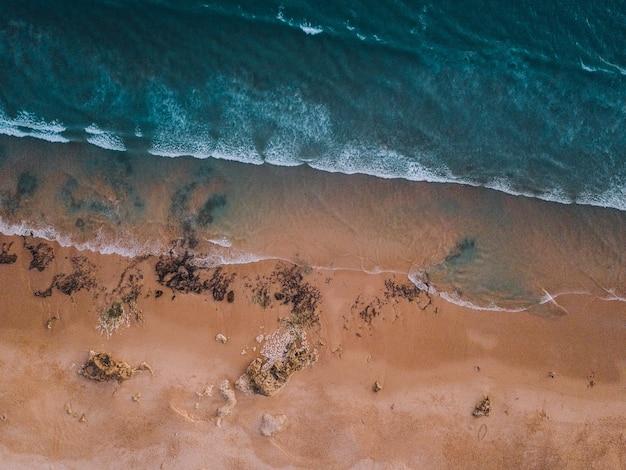 Widok z lotu ptaka na fale morza i piaszczysty brzeg