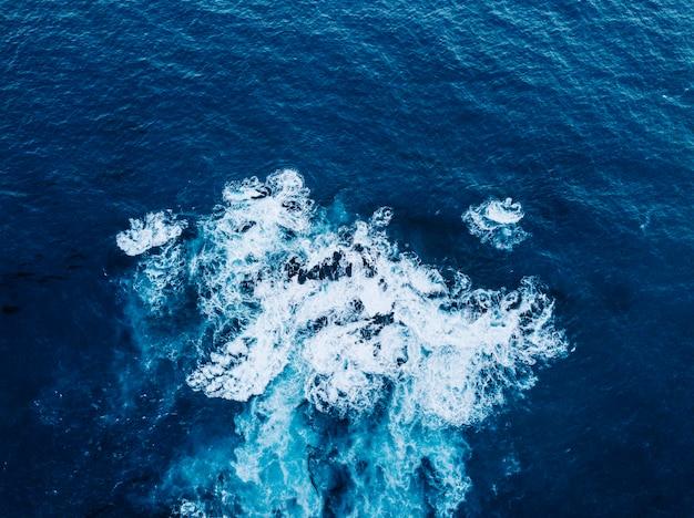 Widok z lotu ptaka na fale rozbijające się na skale. jasna i ciemnoniebieska woda pieni się, a fale przedostają się na brzeg. głębokie morze.