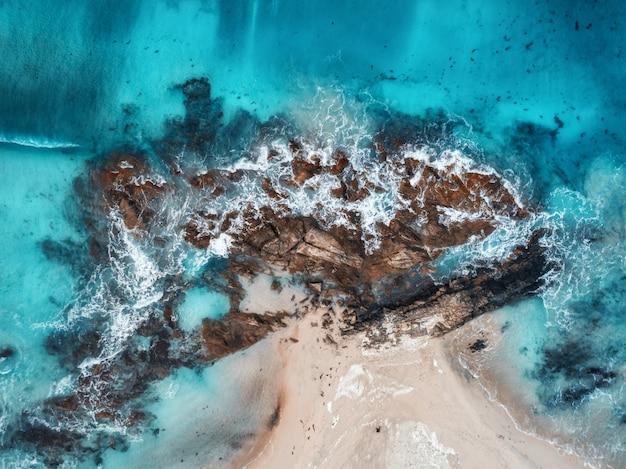Widok z lotu ptaka na fale, skały i przejrzyste morze