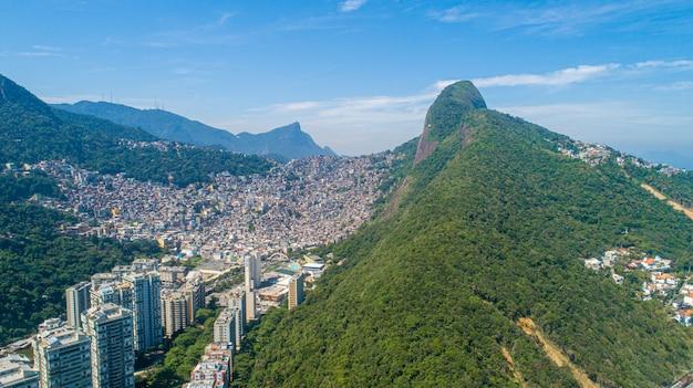 Widok z lotu ptaka na favela da rocinha, największy slums w brazylii na górze w rio de janeiro i panoramę miasta za