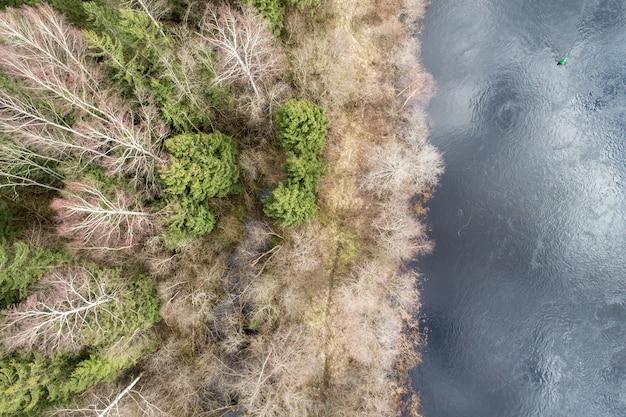 Widok z lotu ptaka na gęsty las z wiecznie zielonymi jesiennymi drzewami porośniętymi odblaskową powierzchnią wody