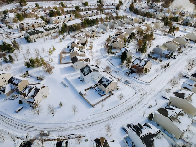 Widok z lotu ptaka na góry krajobrazu zimą miejskich domów mieszkalnych ze śniegiem na zadaszonych domach i drogach.