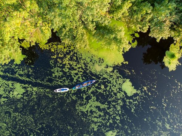 Widok z lotu ptaka na grupę kajaków płynących po leśnej rzece w letni dzień
