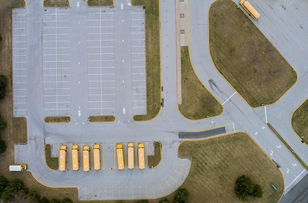 Widok z lotu ptaka na grupę żółtych autobusów szkolnych zaparkowanych w pobliżu liceum