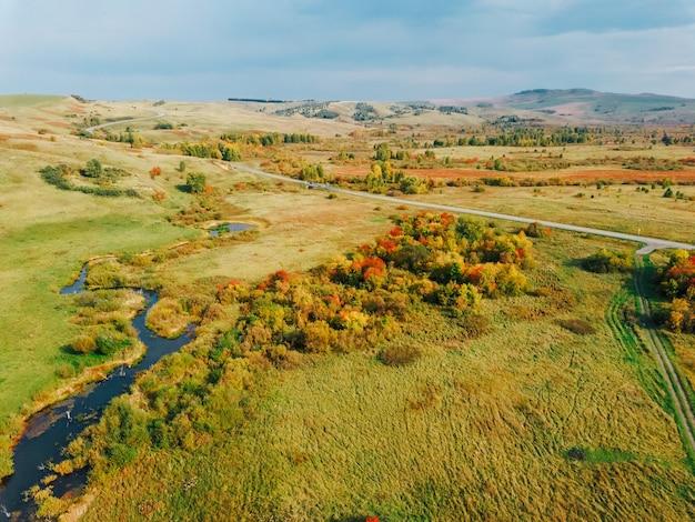 Widok z lotu ptaka na jesienny krajobraz ze wzgórzami i jasnożółtymi kolorami opadających liści.