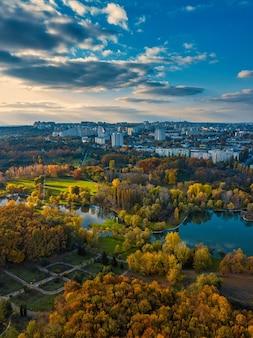 Widok z lotu ptaka na jezioro w parku z jesiennymi drzewami. kiszyniów, mołdawia. epicki lot powietrzny nad wodą. kolorowe jesienne drzewa w ciągu dnia.