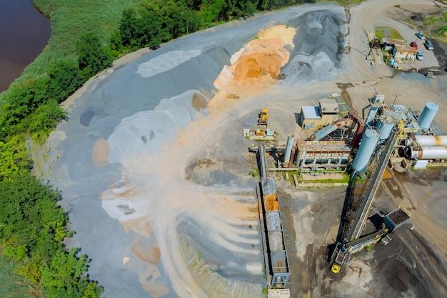Widok z lotu ptaka na kamieniołom panoramy górnictwa odkrywkowego z dużą ilością maszyn w sprzęcie roboczym w zakładzie