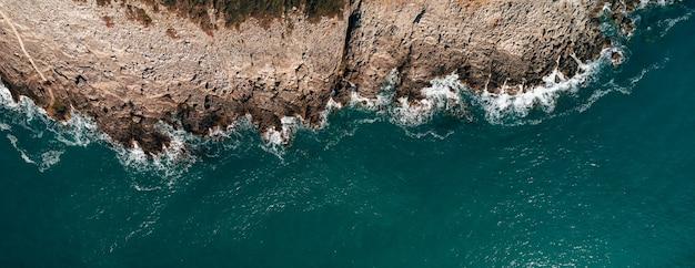 Widok z lotu ptaka na kamienistą plażę i morze z czystą, błękitną wodą na wybrzeżu morza adriatyckiego o zachodzie słońca