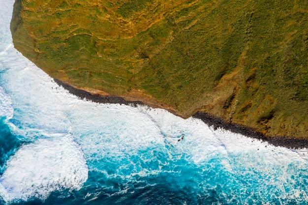 Widok z lotu ptaka na klify wyspy oceanu z ogromnymi białymi falami i krystalicznie niebieską wodą