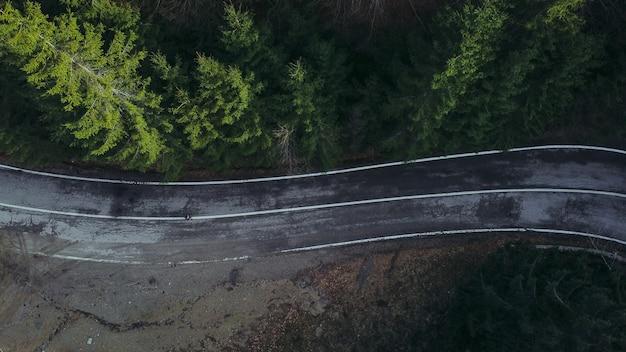 Widok z lotu ptaka na krętą drogę otoczoną zielenią i drzewami