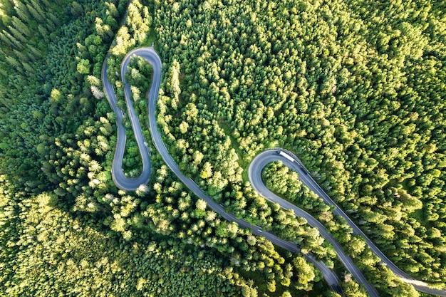 Widok z lotu ptaka na krętą drogę w korytarzu wysokiej przełęczy gęstych zielonych lasów sosnowych.