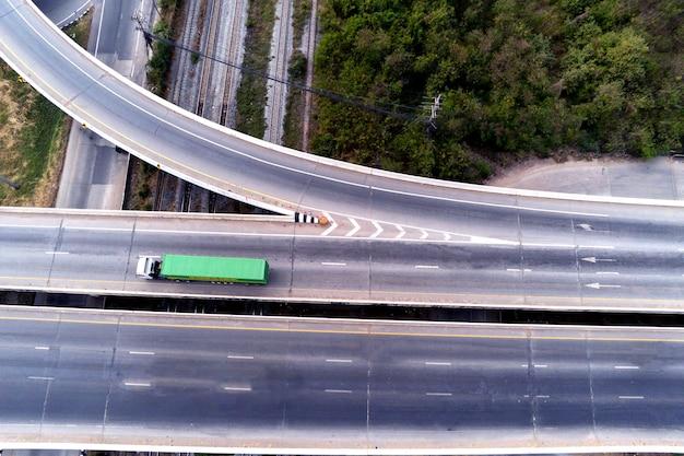 Widok z lotu ptaka na ładunek biały ciężarówka na autostradzie z zielonym pojemnikiem, koncepcja transportu, import, eksport logistyka przemysłowa transport transport lądowy na asfaltowej drodze ekspresowej