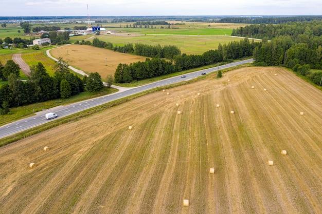 Widok z lotu ptaka na łotewską wieś z autostradą, polami uprawnymi i lasem