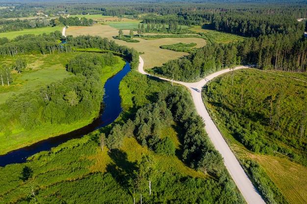 Widok z lotu ptaka na łotewski krajobraz wiejski z krętą rzeką, lasami i drogami wiejskimi o zachodzie słońca
