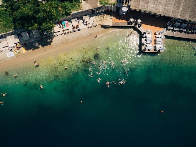Widok z lotu ptaka na ludzi pływających w morskiej kawiarni na plaży nad morzem ludzie kąpią się w zatoce kotorskiej