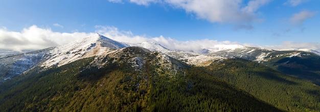 Widok z lotu ptaka na majestatyczne góry pokryte zielonym lasem świerkowym i wysokimi ośnieżonymi szczytami.