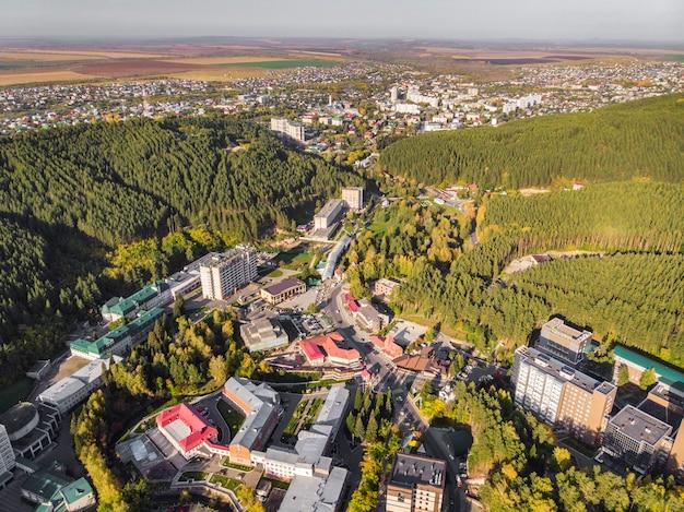 Widok z lotu ptaka na małe miasteczko na terytorium ałtaju. widok z góry na kurort belokurikha. widok z lotu ptaka na domy wśród lasów na zboczach gór.