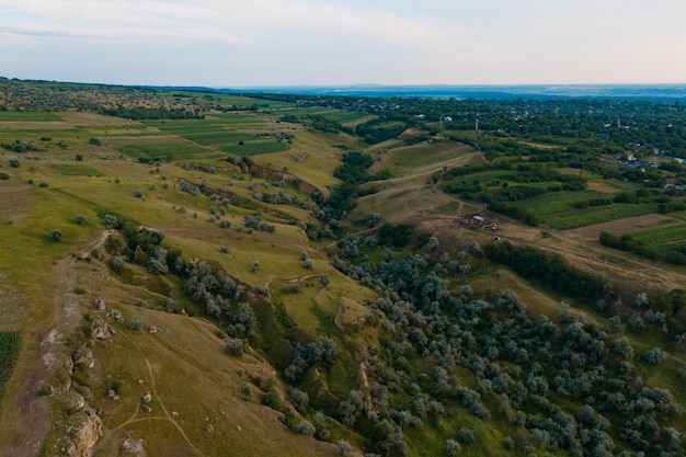 Widok z lotu ptaka na malowniczy krajobraz lądu, drzewa, skały, niebo odbite w wodzie.