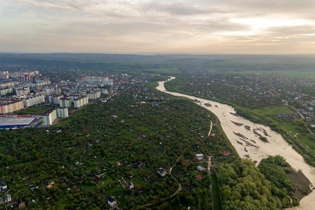 Widok z lotu ptaka na miasto iwano-frankowsk z dzielnicą mieszkaniową i domami na przedmieściach z rzeką pośrodku.