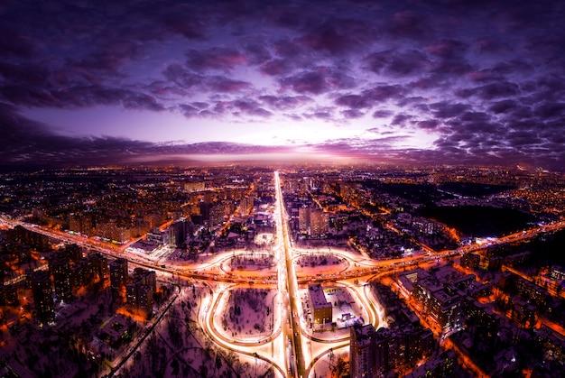 Widok z lotu ptaka na miasto nocą i węzeł komunikacyjny oświetlony latarniami. ciemne nocne niebo.
