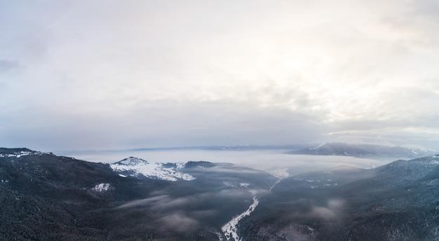 Widok z lotu ptaka na mistyczny krajobraz zimowego lasu górskiego w pochmurny mroźny dzień.