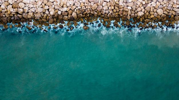 Widok z lotu ptaka na morze rozbijające się o skały