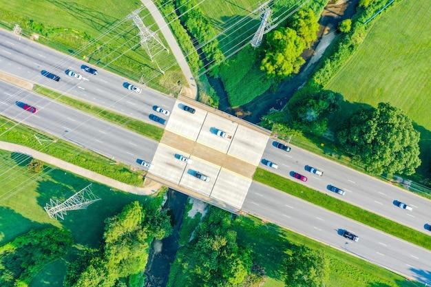 Widok z lotu ptaka na most nad potokiem i linie energetyczne z samochodami na drodze