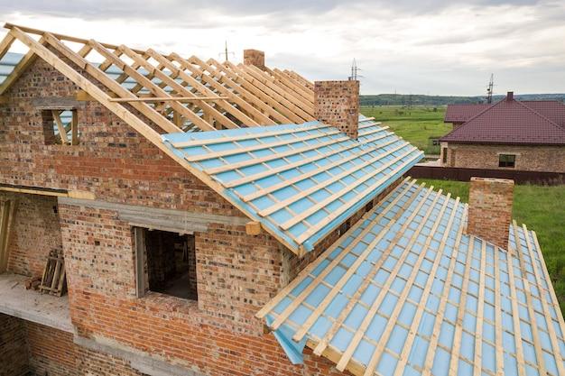 Widok z lotu ptaka na murowany dom z drewnianą ramą dachową w budowie.