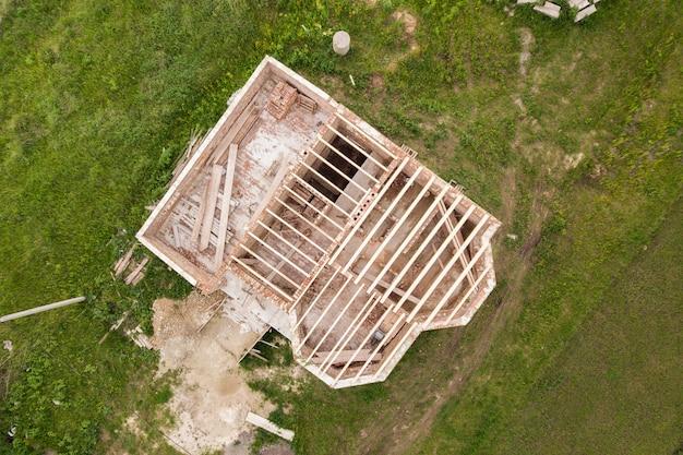 Widok z lotu ptaka na murowany dom z drewnianą ramą stropową w budowie.