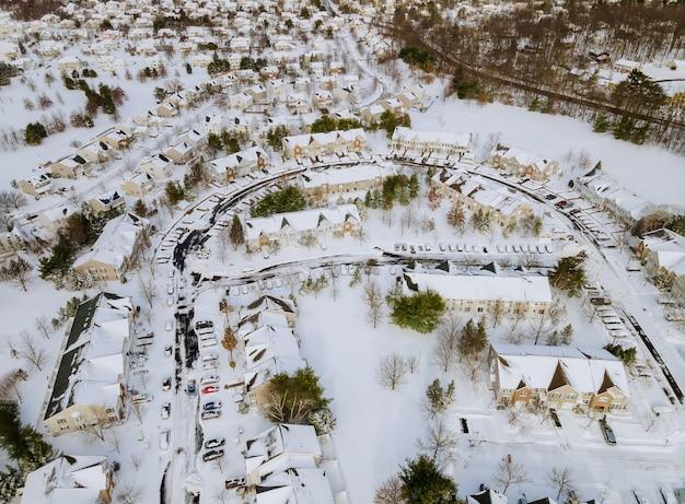 Widok z lotu ptaka na naśnieżane w tradycyjnym osiedlu na przedmieściach w niebezpiecznych warunkach atmosferycznych