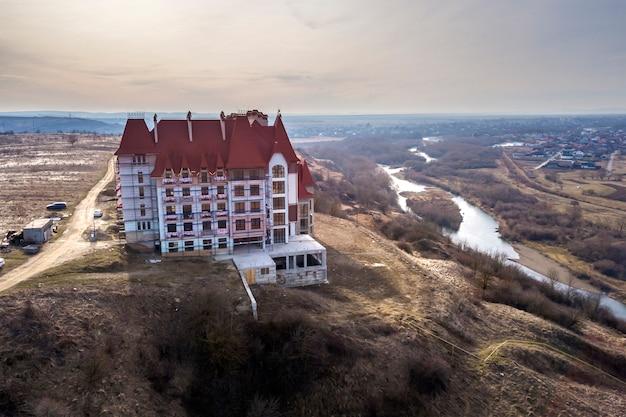Widok z lotu ptaka na niedokończony budynek wielopiętrowy, hotel lub domek ze stiukową ścianą, żeliwnymi balustradami balkonowymi, stromym gontowym dachem i błyszczącymi oknami na tle wiejskiego krajobrazu.