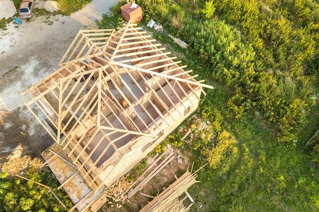 Widok z lotu ptaka na niedokończony dom murowany z drewnianą konstrukcją dachu w budowie.