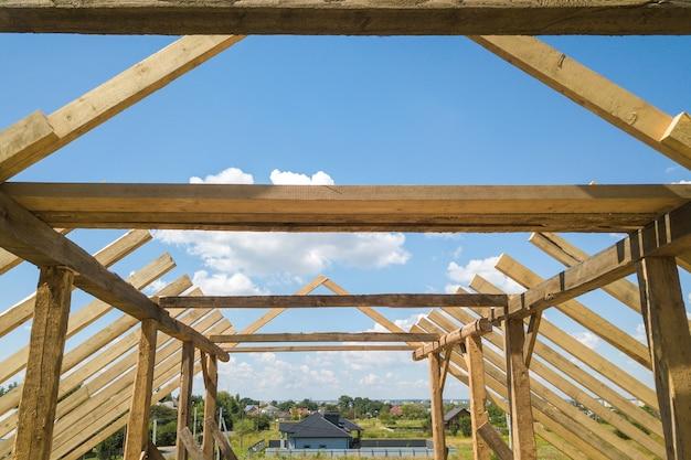 Widok z lotu ptaka na niedokończony dom z drewnianą konstrukcją szkieletową dachu w budowie.