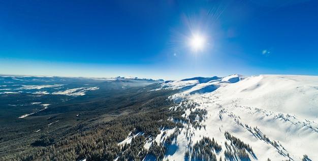 Widok z lotu ptaka na niesamowity, hipnotyzujący widok na zimowy krajobraz górski w słoneczny mroźny dzień w ośrodku narciarskim. koncepcja wakacje w kraju północnej europy. copyspace