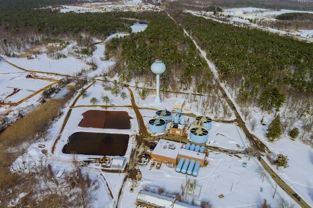 Widok z lotu ptaka na nowoczesną małą przemysłową oczyszczalnię ścieków przy pracy w sezonie zimowym