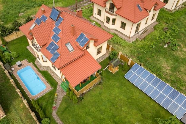 Widok z lotu ptaka na nowy autonomiczny dom z panelami słonecznymi i grzejnikami do ogrzewania wody na dachu oraz na zielony dziedziniec z niebieskim basenem.