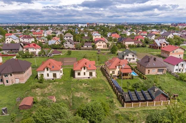 Widok z lotu ptaka na nowy autonomiczny dom z panelami słonecznymi i grzejnikami wody na dachu i zielonym podwórku z niebieskim basenem.