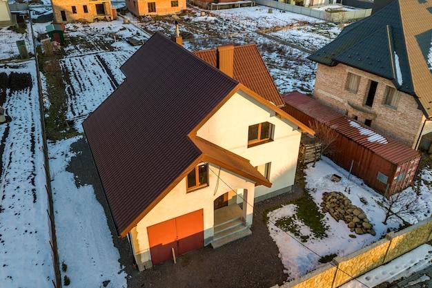 Widok z lotu ptaka na nowy dom mieszkalny i dołączony garaż z dachem gontowym na ogrodzonym podwórku w słoneczny zimowy dzień w nowoczesnej strefie podmiejskiej. idealna inwestycja w wymarzony dom.