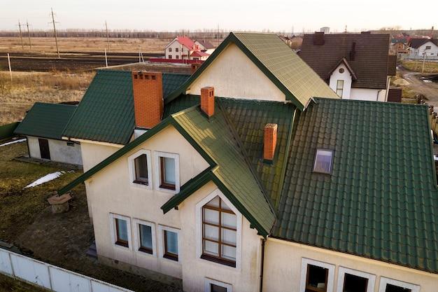 Widok z lotu ptaka na nowy dom mieszkalny i garaż lub stodołę z dachem gontowym na ogrodzonym podwórku w słoneczny dzień.