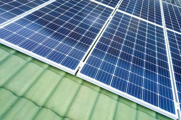 Widok z lotu ptaka na nowy nowoczesny domek mieszkalny z niebieskim błyszczącym systemem fotowoltaicznych paneli słonecznych na dachu. koncepcja produkcji odnawialnej ekologicznej energii zielonej.