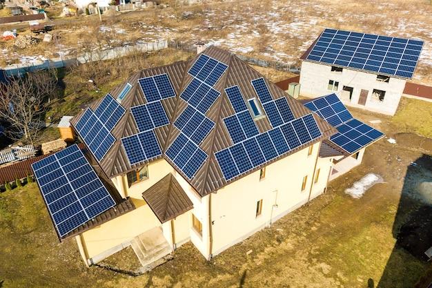 Widok z lotu ptaka na nowy nowoczesny domek mieszkalny z niebieskim błyszczącym systemem fotowoltaicznych paneli słonecznych na dachu