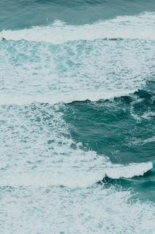 Widok z lotu ptaka na ocean z falami i skałami w jasny dzień, relaksująca scena w odcieniach błękitu
