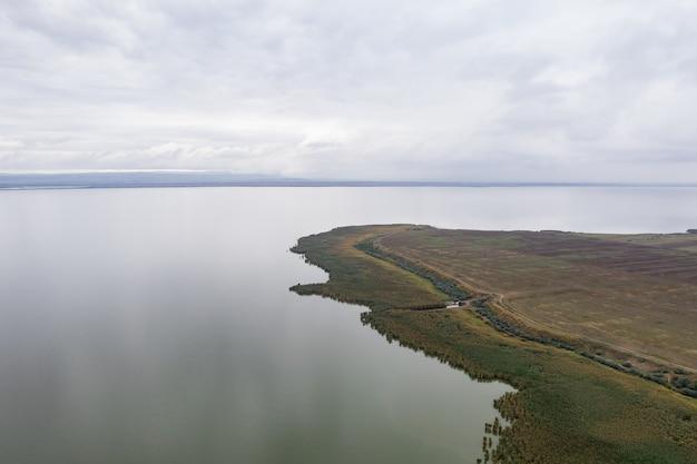 Widok z lotu ptaka na ogromne jezioro z zielenią i wieczornym niebem