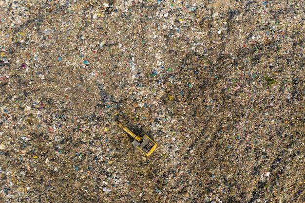 Widok z lotu ptaka na ogromne wysypisko śmieci z dużą koparką.