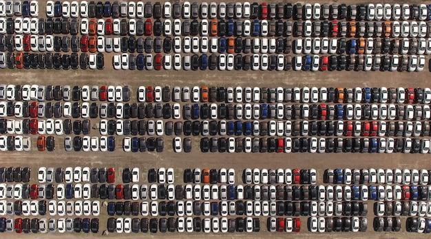 Widok z lotu ptaka na ogromny parking magazynowy z nowymi samochodami