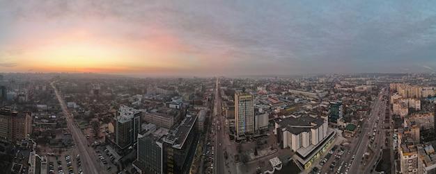 Widok z lotu ptaka na panoramę kiszyniowa o zachodzie słońca. wiele budynków biurowych i mieszkalnych, drogi z wieloma samochodami.