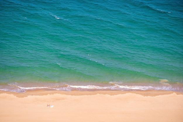Widok z lotu ptaka na piaszczystą plażę z błękitnymi falami morskiej wody w kurorcie nha trang