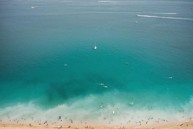 Widok z lotu ptaka na piaszczystej plaży z turystami, pływanie w pięknej, czystej wodzie morskiej i jacht z widoku z góry.