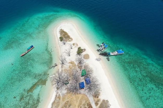 Widok z lotu ptaka na piękną czystą wodę i białą plażę z łodziami latem na tropikalnej wyspie